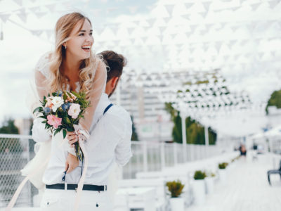 Elegant blonde in a white dress. Couple standing in a park. Bride with bouquet of flowers. Man in a white shirt